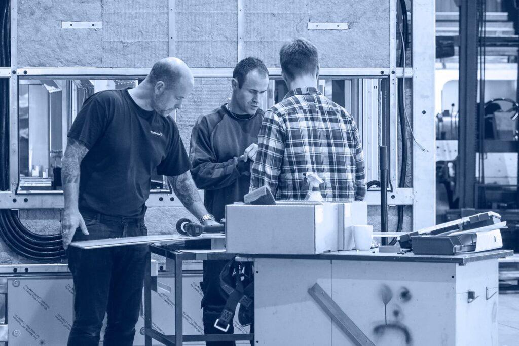 3 personer arbejder på et værksted